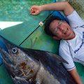 釣り上げたカジキと横に寝ている男