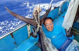 釣り上げたカジキとピースサインの男