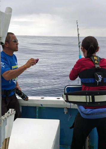 カジキを釣っている女性と写真を撮る鶴巻船長