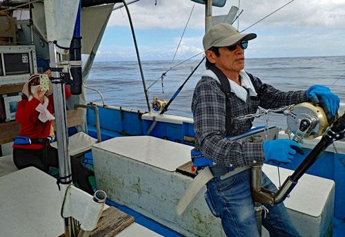 カジキを釣っている男性と後ろで動画を撮影する娘
