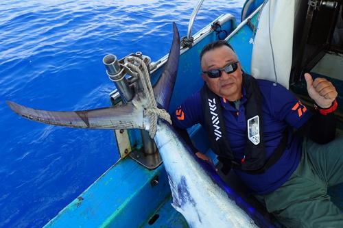 自ら釣り上げたカジキと記念撮影している男性
