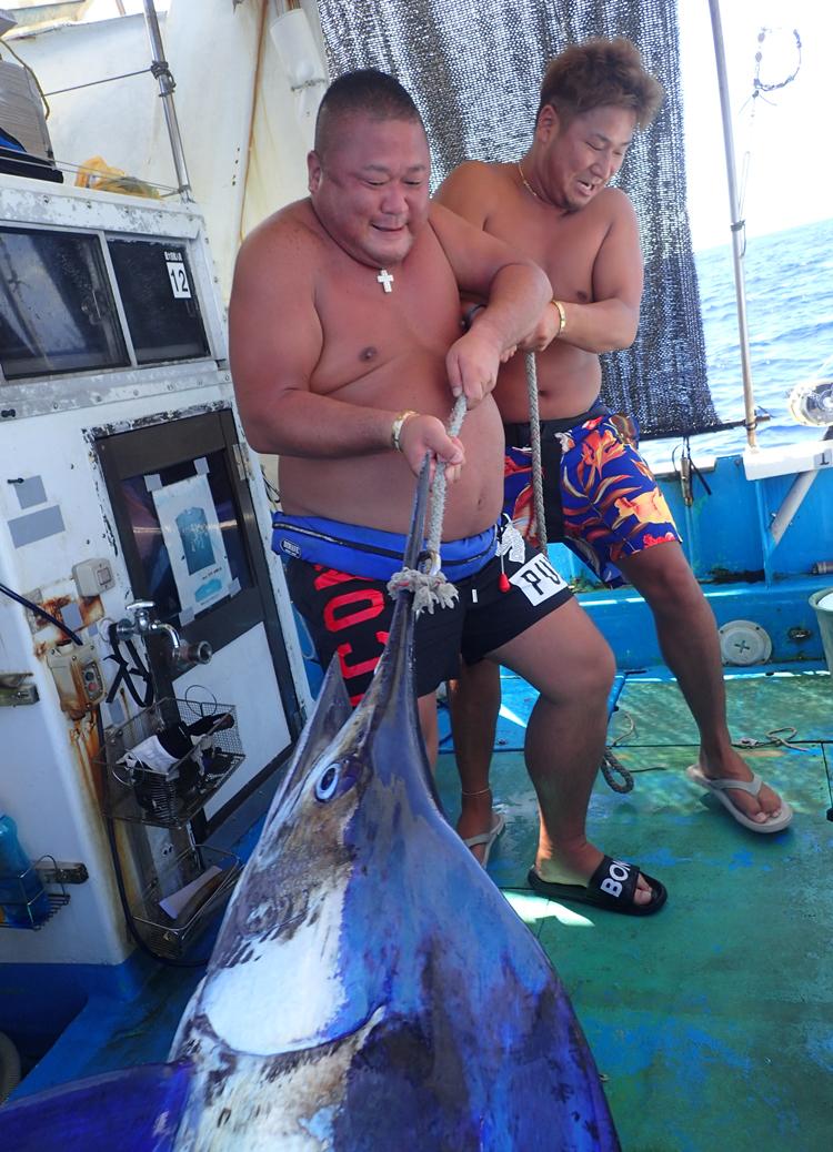 カジキを引き上げる男性二人