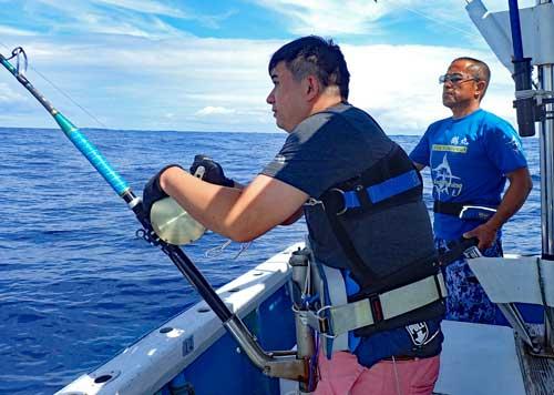 沖縄でカジキ釣りをしている香港から来た男性