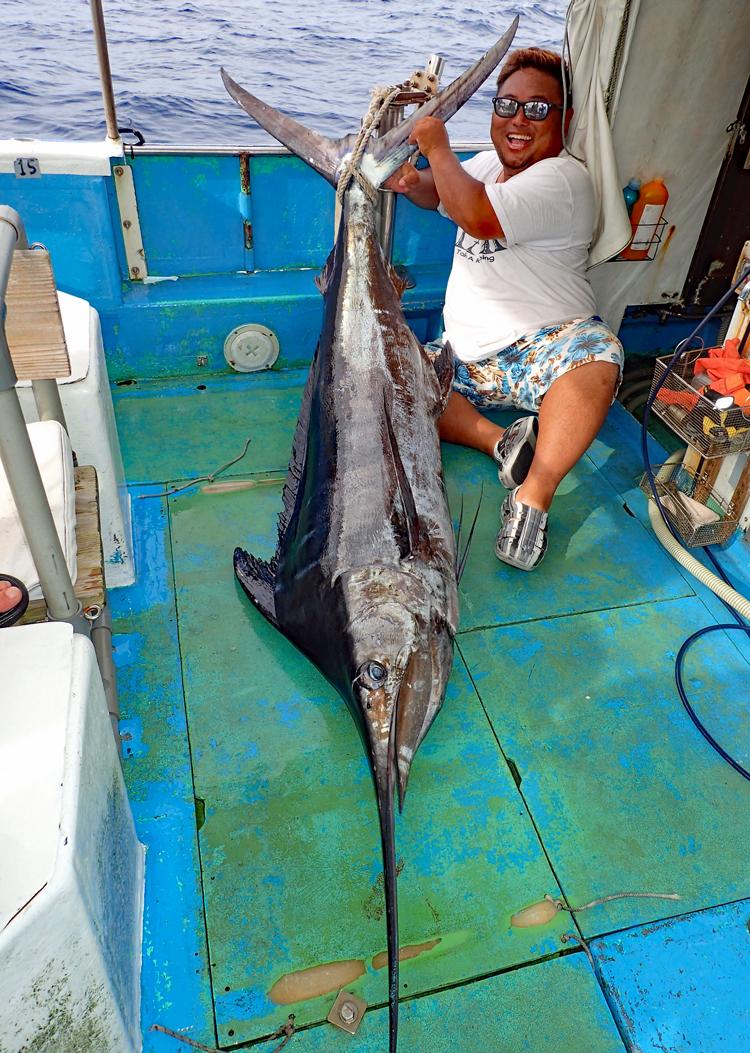 沖縄のトローリングで釣れたカジキと日焼けしたサングラスの男性