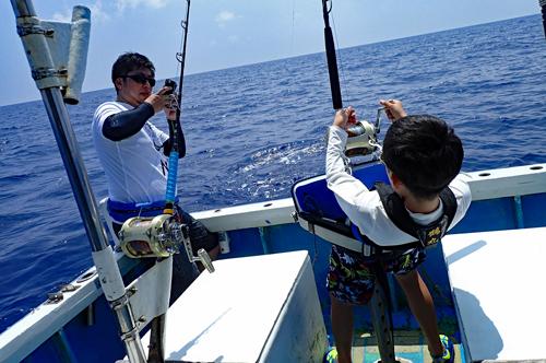 トローリングでオニカマス/バラクーダを釣っている10才の少年