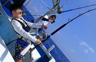 トローリングでバラクーダを釣っている10才の少年と後ろで撮影する父