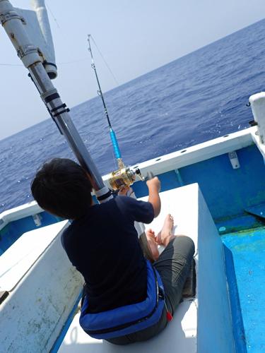 トローリングでマグロを釣っている少年の後ろ姿