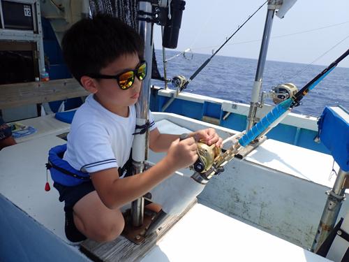 トローリングでマグロを釣っている少年