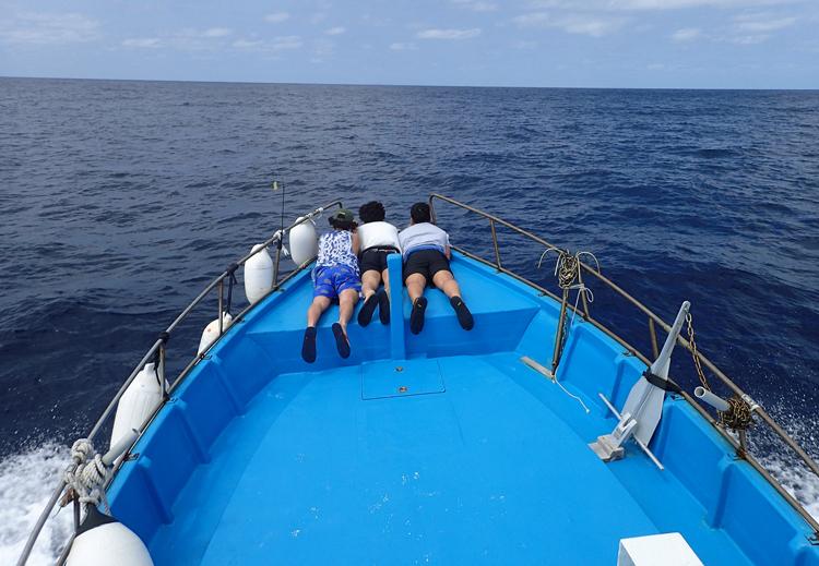鶴丸の船首でうつぶせになり海を見ている3人の男性