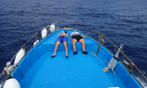 鶴丸の船首で寝ている男性2人