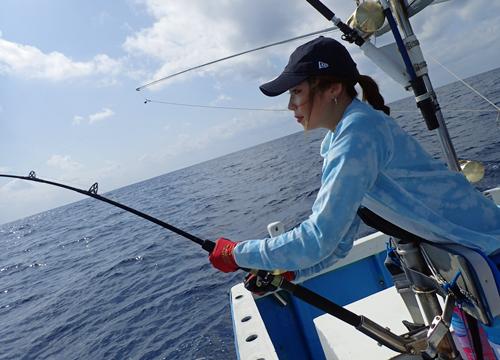 トローリングでカツオを釣っている女性