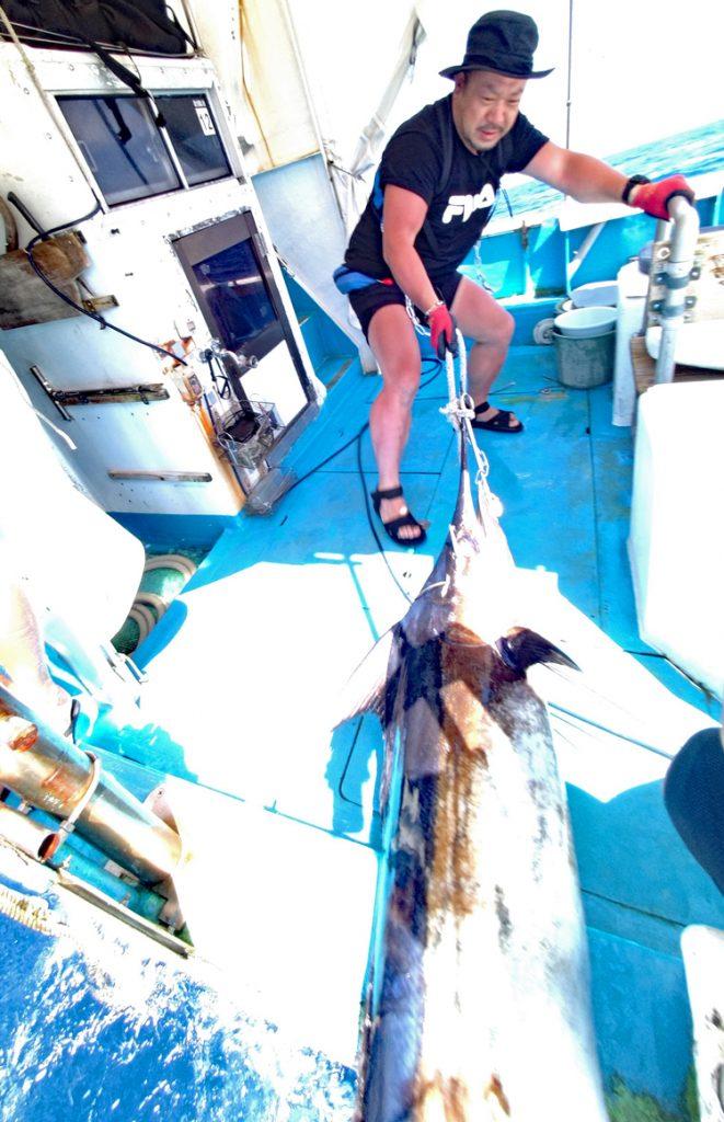 カジキを船に引き上げる男性