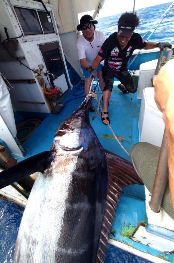 クレーンズ沖縄のトローリングで120kgのカジキを船に引き上げる滋賀県と京都府から釣りに来た男性