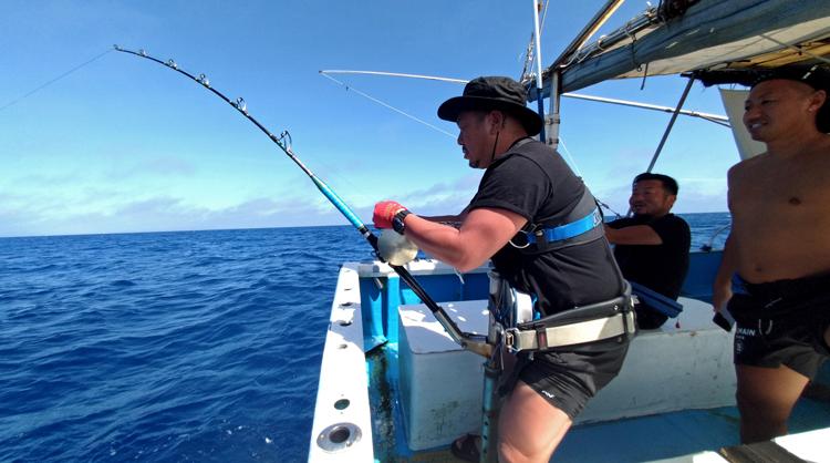 カジキを釣っている男性と後ろで見守る二人の男