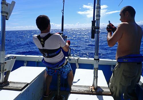 カジキを釣っている男性を撮影する男