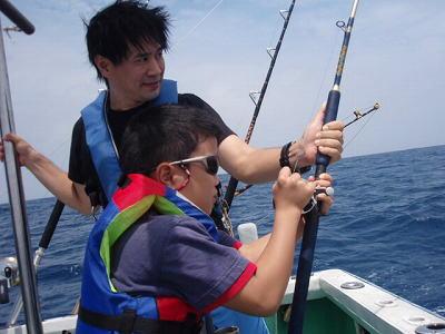 魚と格闘中の子供