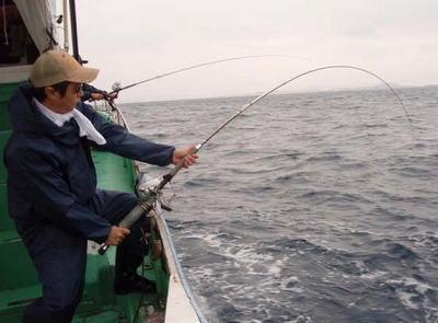魚と格闘中の男性