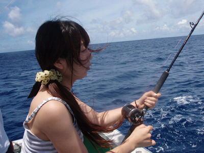 魚とファイト中の女性